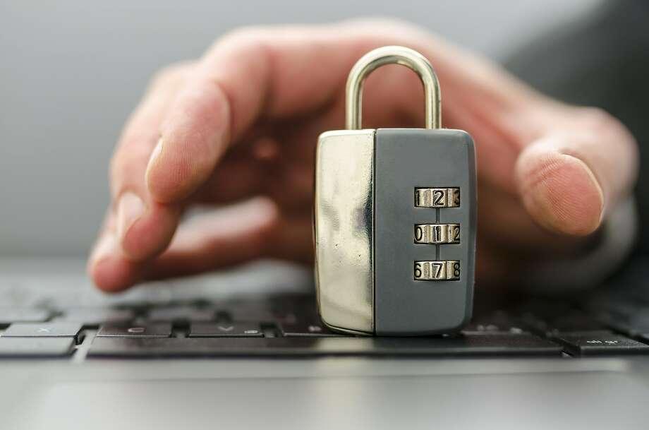 Male hand stealing padlock off computer keyboard. Photo: Gaj Rudolf, Gajus - Fotolia