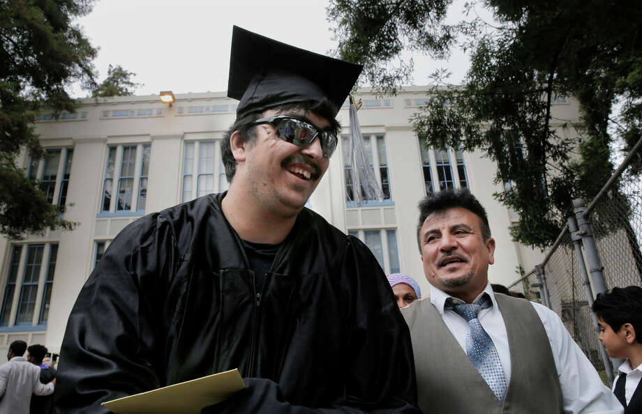 Top: Saleh Khalaf and father Raheem smile after Wednesday's graduation ceremonies in Oakland. Above: When Saleh was treated at Children's Hospital Oakland, Raheem would comfort him to sleep. Photo: Michael Macor / Michael Macor / The Chronicle / ONLINE_YES