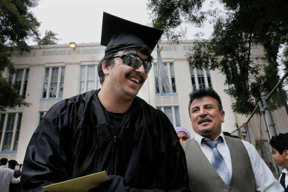 Top: Saleh Khalaf and father Raheem smile after Wednesday's graduation ceremonies in Oakland. Above: When Saleh was treated at Children's Hospital Oakland, Raheem would comfort him to sleep.