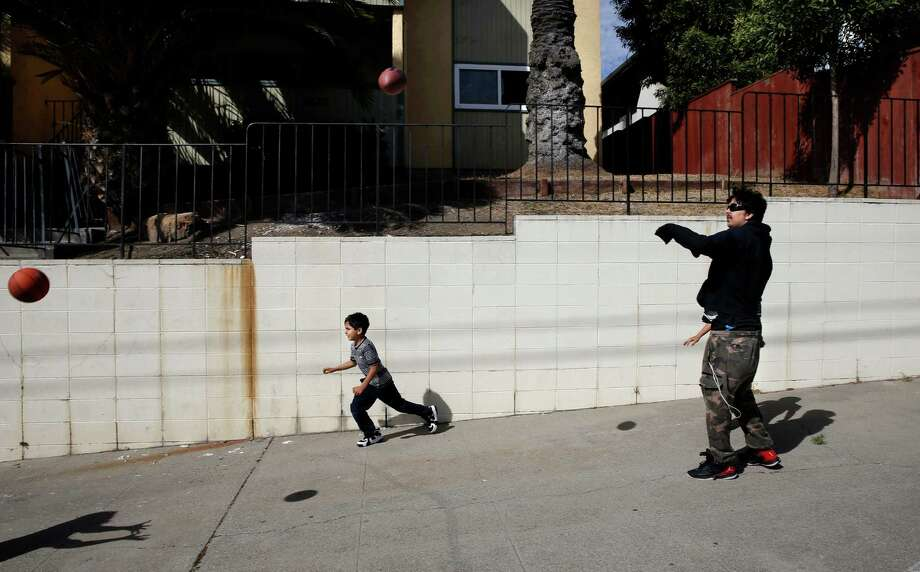 Saleh Khalaf plays catch with brother Jay, 7, in front of their Oakland home. Saleh endured a dozen surgeries and nearly died several times of his injuries in Iraq. Photo: Michael Macor / Michael Macor / The Chronicle / ONLINE_YES