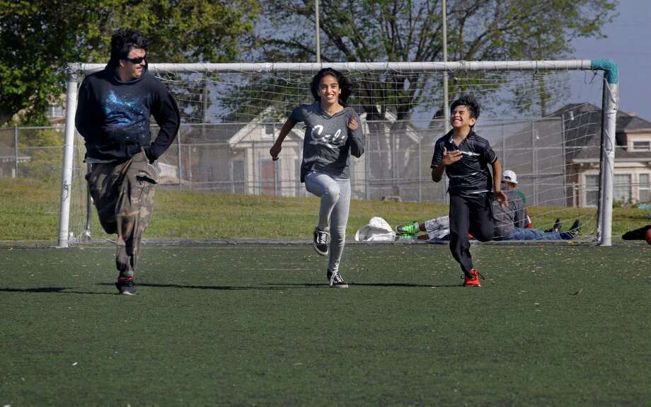 Saleh Khalaf, (left) runs a foot race with his sister Marwa, 13 and brother Ali, 10 at the park across the street from their home in Oakland, Calif., on Sun. May 31, 2015. Khalaf now 20-years-old was the boy they called Lion Heart, who nearly died in a bomb explosion in Iraq in 2003 and then traveled to Children's Hospital Oakland for multiple surgeries which saved his life. Photo: Michael Macor / The Chronicle / ONLINE_YES