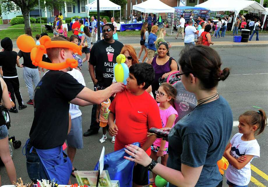 "Balloon Louie, based in Stratford, places a balloon parrot onto the shoulder of Zachary Allen, 8, during 5th Annual ""Main Street Festival"" in downtown Stratford, Conn., on Saturday June 6, 2015. The festival is sponsored by Stratford Rotary and the Stratford Chamber of Commerce. According to the festival's website: www.stratfordctfestival.org, ""This will be an opportunity for various organizations and vendors to promote the work they do, boost their treasury dollars, and provide a day of fun and pleasure for people of all ages."" Photo: Christian Abraham, Staff Photographer / Connecticut Post"