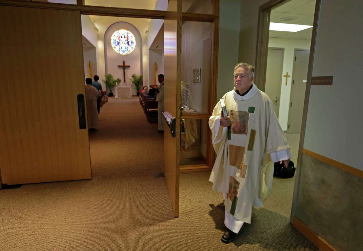 """Father Norbert Maduzia of St. Ignatius Loyola Catholic Church says he loves being a priest, but """"sometimes I laughingly say I want to get in my car and drive until I run out of gas."""" He often gets home minutes before 3 a.m. but still gets up at 5:30 a.m. for work."""