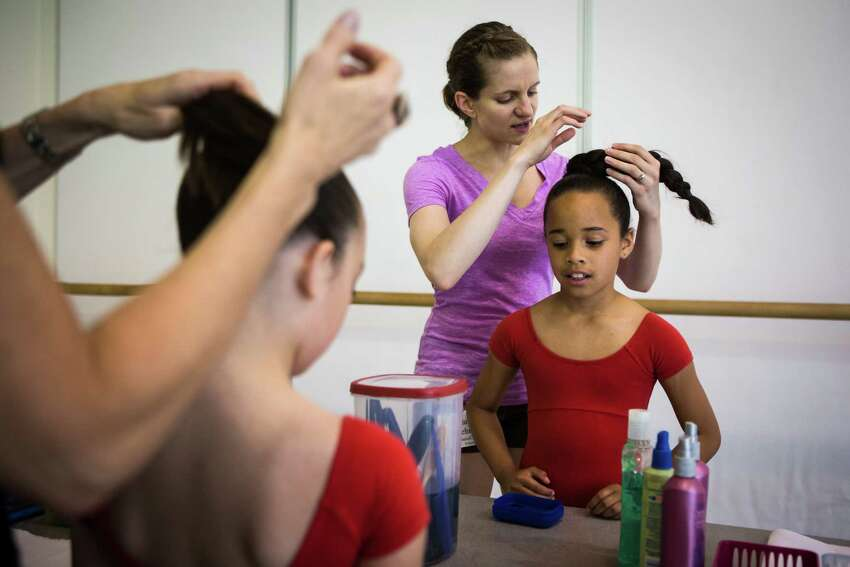 Laila Vieira, right, gets her hair done before performing in Pacific Northwest Ballet's 21st annual DanceChance Observation Day on Saturday, June 6, 2015. The program offers full scholarships for students to train twice a week with the PNB School. The performance showcased the dancers' hard work for friends, family and supporters of the program.