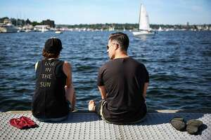 Jack Johnson and Nick Hughes look out over Lake Union during a heat wave across the Pacific Northwest on Saturday, June 6, 2015. Temperatures climbed into the lower 80s in the Seattle area, drawing scores of people to area parks, beaches and water fountains.