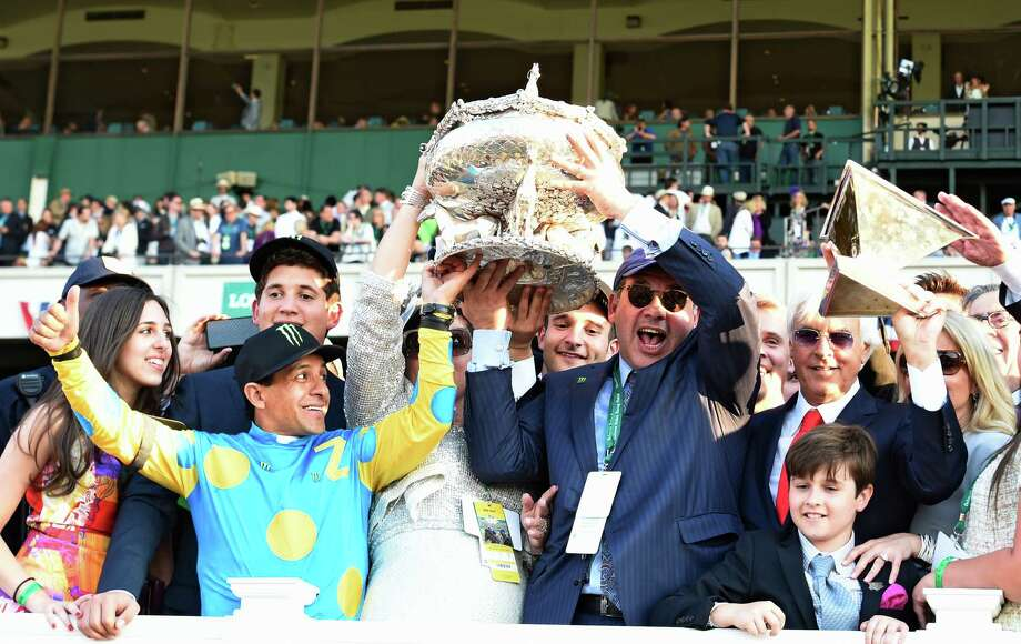American Pharoah's owner Ahmed Zayat holds the Belmont Stakes Trophy aloft, center with the help of jockey Victor Espinoza, left as trainer Bob Baffert raises theTriple Crown trophy aloft after his trainee made his way to the record books by winning the 147th running of the Belmont Stakes and thoroughbred racing's Triple Crown June 6, 2015 at Belmont Park in Elmont, N.Y.   (Skip Dickstein/Times Union) Photo: SKIP DICKSTEIN, ALBANY TIMES UNION