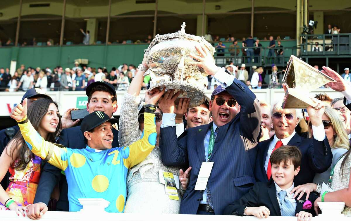 American Pharoah's owner Ahmed Zayat holds the Belmont Stakes Trophy aloft, center with the help of jockey Victor Espinoza, left as trainer Bob Baffert raises theTriple Crown trophy aloft after his trainee made his way to the record books by winning the 147th running of the Belmont Stakes and thoroughbred racing's Triple Crown June 6, 2015 at Belmont Park in Elmont, N.Y. (Skip Dickstein/Times Union)