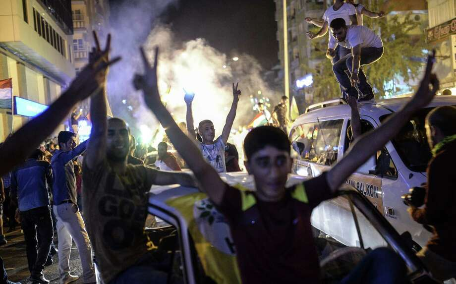 Supporters of the pro-Kurdish Peoples' Democratic Party (HDP) celebrate in the streets the results of the legislative election, in Diyarbakir on June 7, 2015. The HDP easily surpassed the 10 percent barrier needed to send MPs to parliament. Under Turkey's proportional representation system, this means the Turkey's Islamic-rooted Justice and Development Party (AKP) will need to form a coalition for the first time since it first came to power in 2002. AFP PHOTO / BULENT KILICBULENT KILIC/AFP/Getty Images Photo: BULENT KILIC, Stringer / AFP / Getty Images / AFP