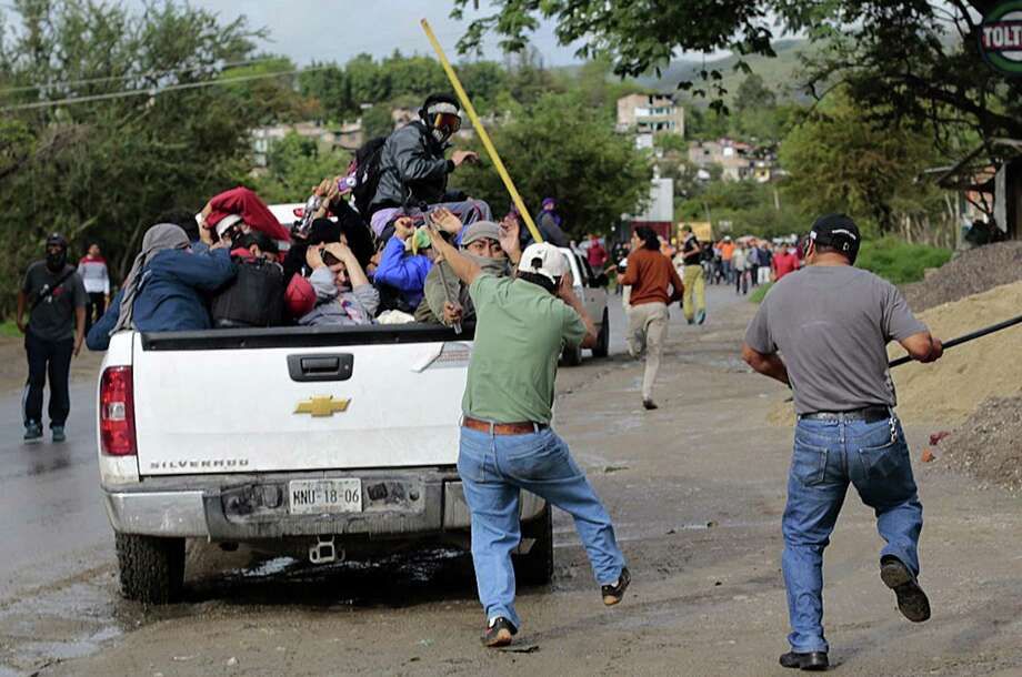 In an attempt to halt elections, residents Sunday attack a pickup carrying students from the school of Ayotzinapa near a voting station in Tixtla, Mexico. Photo: PEDRO PARDO, Stringer / AFP