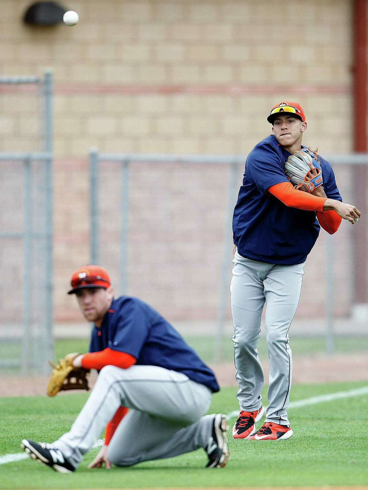 Houston Astros infielder Carlos Correa (76) throws over Houston Astros infielder Nolan Fontana (78) during Houston Astros spring training workouts at the Osceola County facility, Friday, Feb. 27, 2015, in Kissimmee.