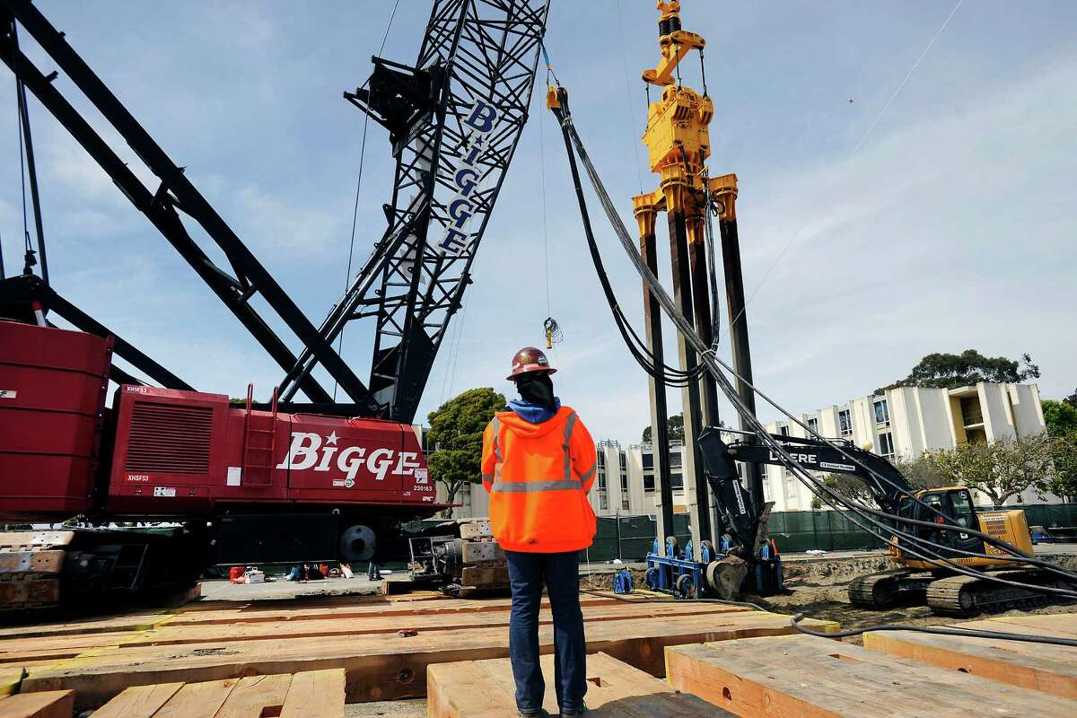 The 53-ton, 75-foot-long Jafec 40,000 Direct Power Compactor hangs from a crane during a test run of the machinery to compact soil on Treasure Island.