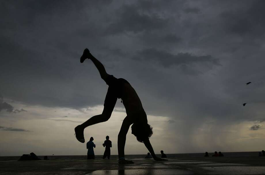 A boy practices somersault on the shore of the Arabian Sea during pre monsoon rains in Mumbai, India, Sunday, June 7, 2015. The monsoon rains have arrived in the southern most parts of the country.  Photo: Rafiq Maqbool, Associated Press