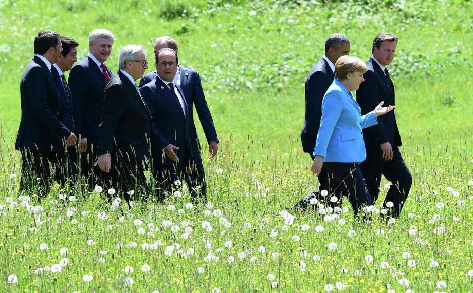 TOPSHOTS  (LtoR) Italy's Prime Minister Matteo Renzi, Japanese Prime Minister Shinzo Abe, Canada's Prime Minister Stephen Harper, European Union Commission President Jean-Claude Juncker, French President Francois Hollande, President of the European Council Donald Tusk, US President  Barack Obama, Germany's Chancellor Angela Merkel and British Prime Minister David Cameron walk to pose for a family picture on they way to their first working session at the Elmau Castle near Garmisch-Partenkirchen, southern Germany, on June 7, 2015 at the start of a G7 summit. Germany hosts a G7 summit at the Elmau Castle on June 7 and June 8, 2015.  AFP PHOTO / JOHN MACDOUGALLJOHN MACDOUGALL/AFP/Getty Images Photo: JOHN MACDOUGALL, Staff / AFP