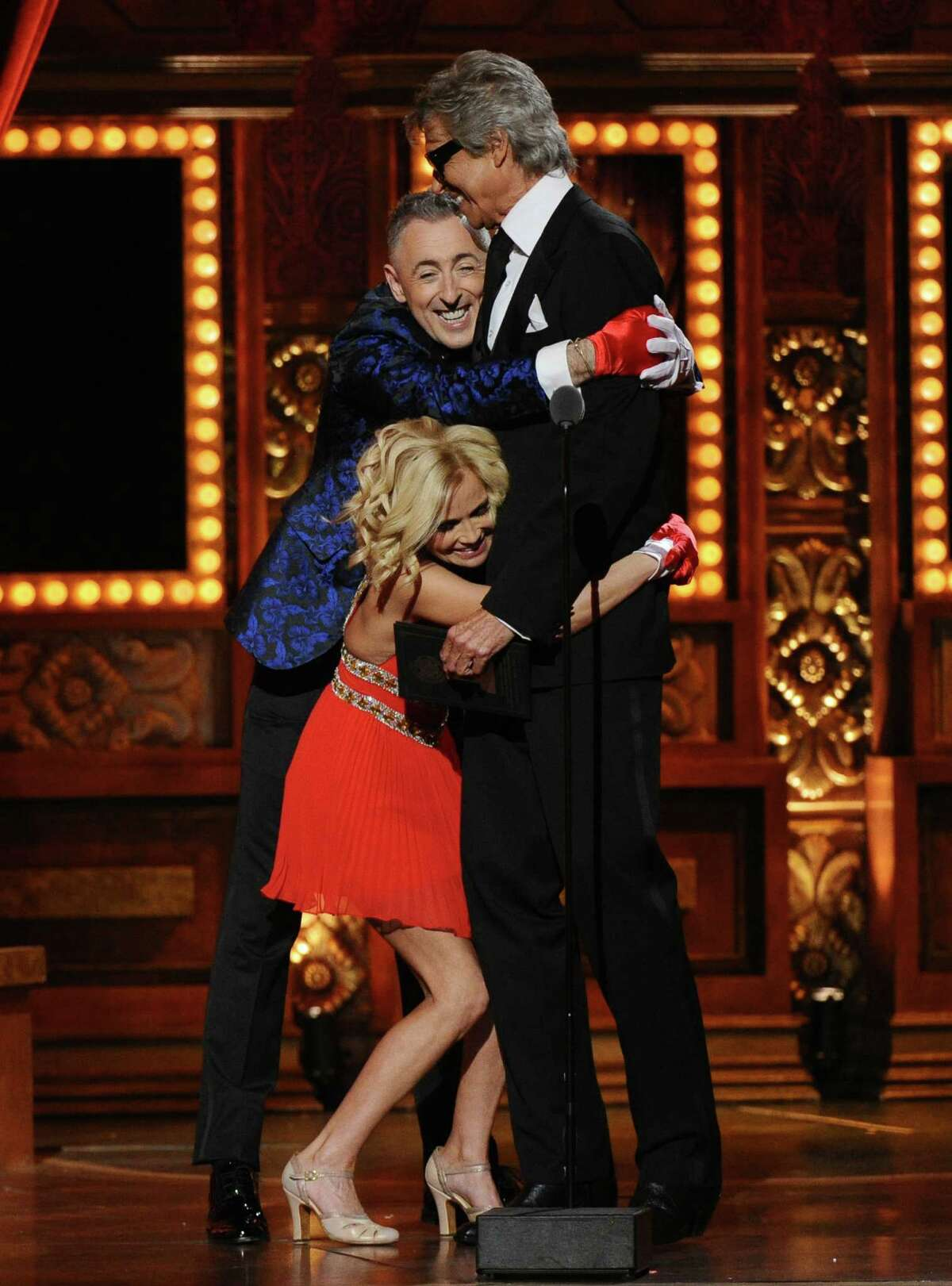 Alan Cumming, and Kristin Chenoweth embrace Tommy Tune, right, winner of the lifetime achievement award at the 69th annual Tony Awards at Radio City Music Hall on Sunday, June 7, 2015, in New York. (Photo by Charles Sykes/Invision/AP)