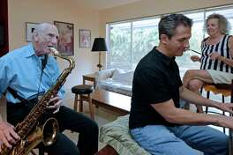 Al Karp (left) plays the saxophone as he rehearses with son Larry and wife Saundra at their home in North Miami Beach, Fla. The trio performs old standards as the Karp Family to ease stress and help raise money to save their home from foreclosure.