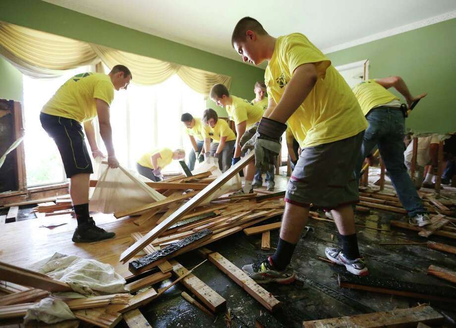 Missionaries from the Texas Houston South Mission clean out Tom and Leigh Killian's Meyerland home.  Photo: Jon Shapley, Staff / © 2015 Houston Chronicle