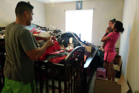 Sergio Herrera packs personal items from flooded apartment in preparation for FEMA help while wife Maria Herrera comforts daughter Eiza Herrera, 1, at The Crossings apartment complex on Sunday, June 7, 2015, in Houston. ( Mayra Beltran / Houston Chronicle )