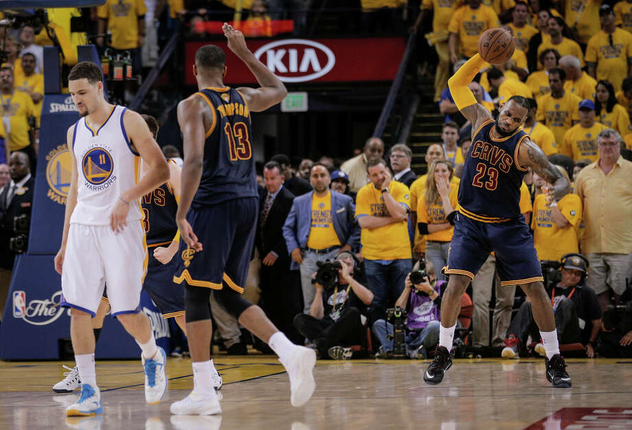 Cleveland's LeBron James slams the ball to celebrate his team's 95-93 overtime victory at Oracle Arena, as the Warriors' Klay Thompson (11) walks away. The Cavaliers' win means the series is certain to return to Oakland. Photo: Carlos Avila Gonzalez / The Chronicle / ONLINE_YES