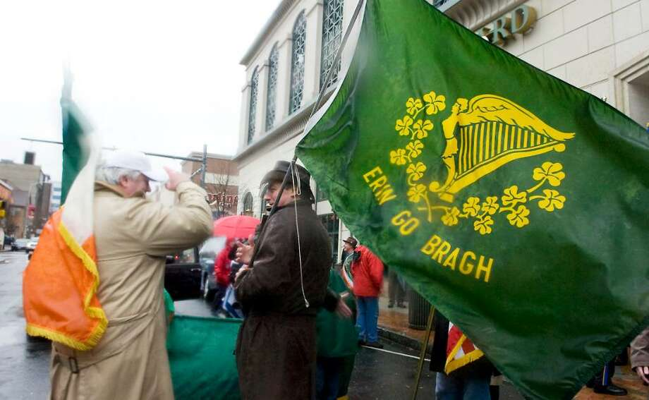 Members of the Ancient Order of Hibernians hold on to their hats and their flags as they brave the elements and march in the Annual St. Patrick's Day Parade last year in Stamford. Photo: Kathleen O'Rourke / Stamford Advocate