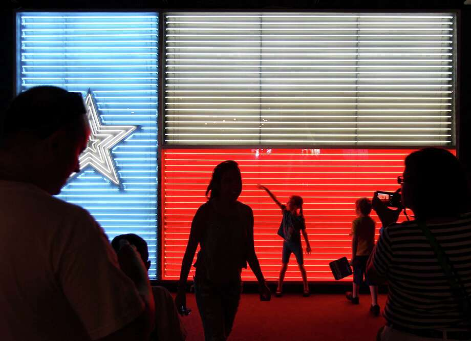 Guests walk past and pose at the popular neon Texas flag inside the Institute of Texan Cultures at the 2014 Texas Folklife Festival. Photo: Kin Man Hui /San Antonio Express-News / ©2014 San Antonio Express-News
