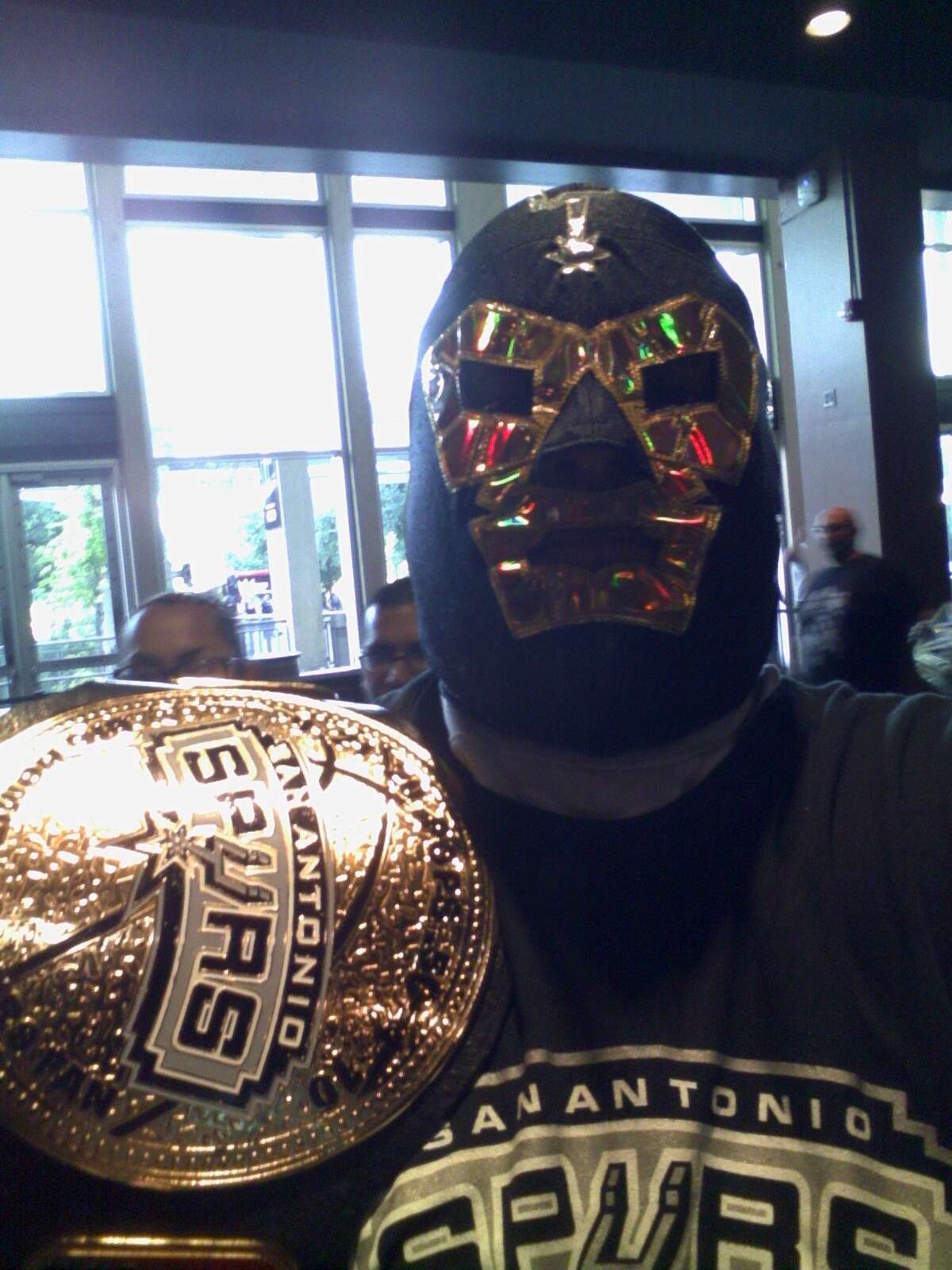 This Spurs fan, otherwise known as the Spurs Big Homie, dons a silver and black luchador mask complete with a title belt.