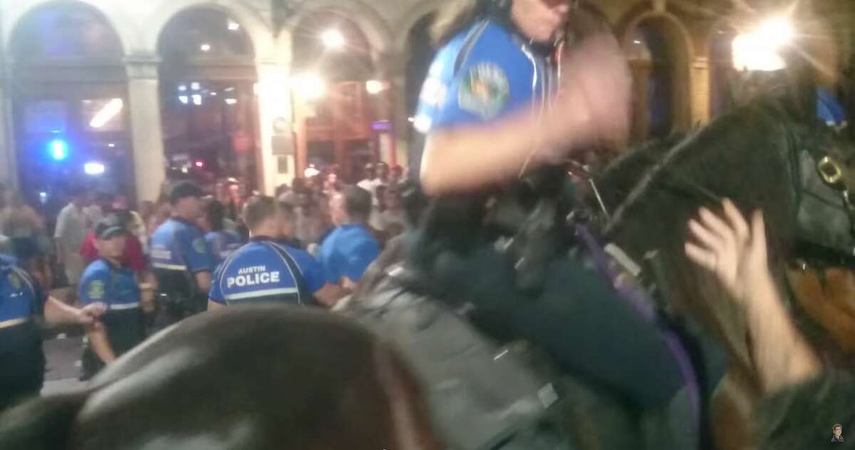 A video published on YouTube on Sunday shows mounted horse patrol officers for the Austin Police Department pushing people and circling an area in the 400 block of E. Sixth St. moments where an officer tackled a man early Sunday morning. In the video, a mounted officer snatches a bystander's phone as he records the incident and throws it on the ground. Another officer, on foot, then apparently sprays the same man with mace.