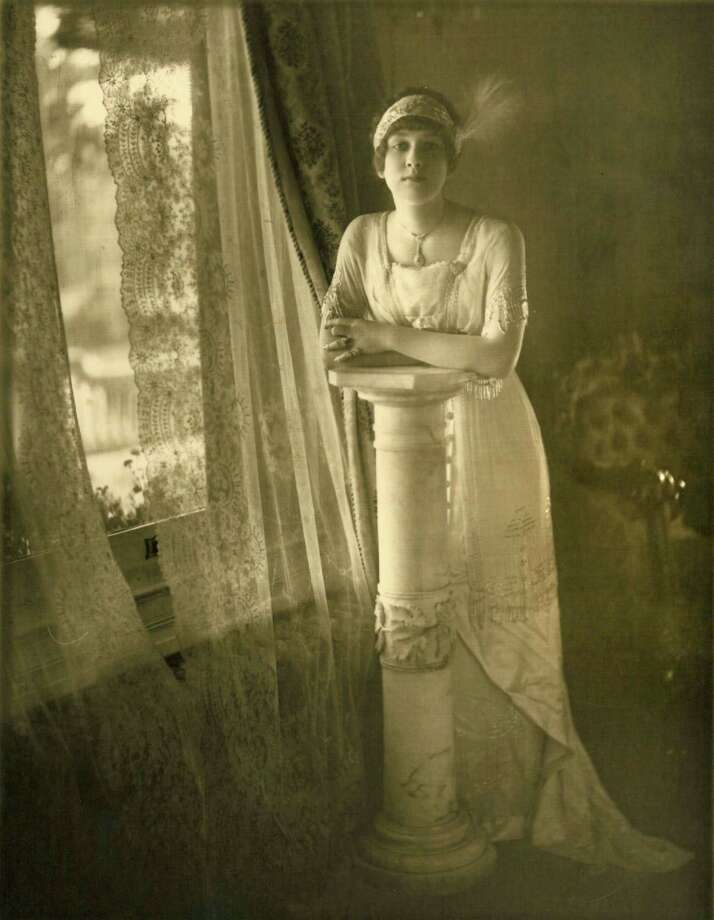 Mamie Louise McFaddin, estimated at 16, wearing her debutant dress in the McFaddin-Ward House parlor around 1911.  Mamie saved several postcards from friends and family which McFaddin-Ward House Museum archived.  Photo provided by McFaddin-Ward House Museum