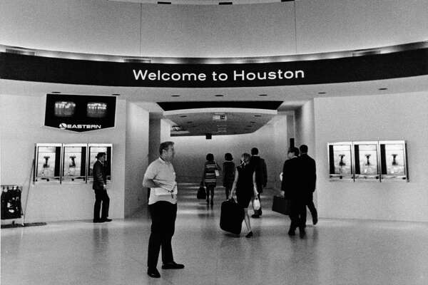 "06/1969 - Travelers are greeted with a ""Welcome to Houston"" sign as they enter the main terminal from the Eastern Airlines gates at Houston Intercontinental Airport."