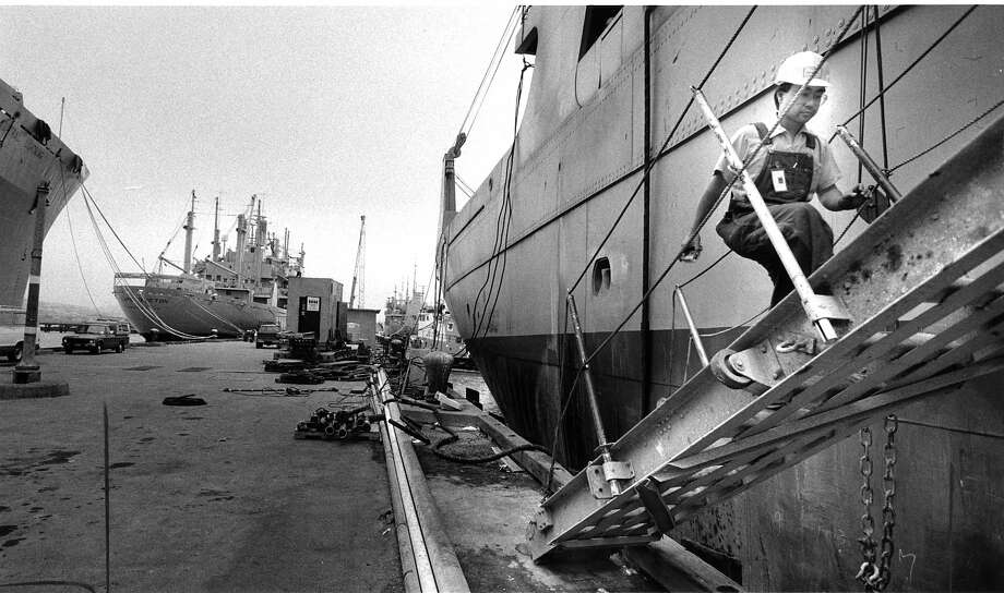 A shipworker at Hunters Point Naval Shipyards boards the Cap Borda to help prepare it for deployment to the Middle East. The Cape Breton in the background is another dry cargo supply ship which is being activated  from the Ready Reserve Force for Middle East duty.  Photo ran 08/25/1990, p. A1 Photo: Michael Maloney, The Chronicle