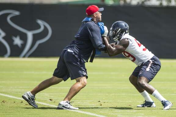 Houston Texans special teams assistant coach Doug Colman, left, runs a drill with linebacker Whitney Mercilus (59) during Texans' organized team activities at the Methodist Training Center Monday, June 8, 2015, in Houston.  ( Brett Coomer / Houston Chronicle )