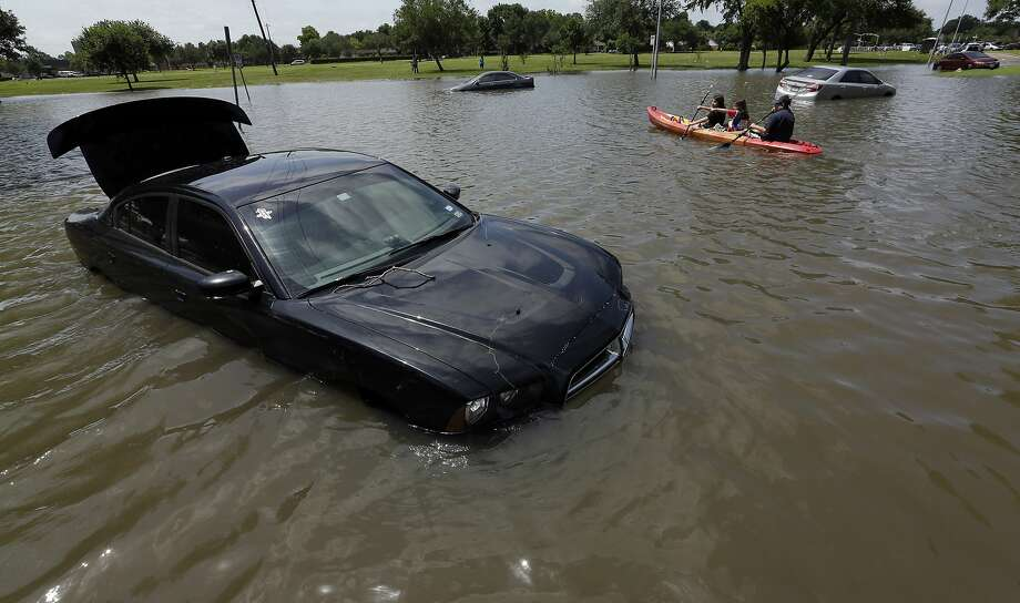 Boaters paddle past cars submerged in floodwaters on a Houston street on May 26. Texas, like most of the country, had its wettest month ever, and its five-year drought was washed away in just one month. Photo: David J. Phillip, Associated Press