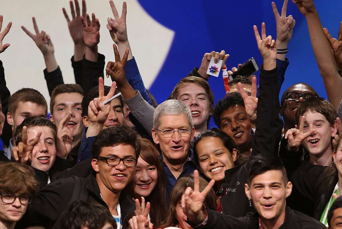 Apple CEO Tim Cook (middle) poses with some of the 350 students who received scholarships to attend the WWDC15 conference at Moscone West in San Francisco, California, on Monday, June 8, 2015.