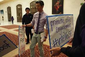 Allen Lu, a SF Youth Commission employee, hands signs out to students before a rally held by the San Francisco Youth Commission at City Hall in San Francisco, Calif. Monday, March 16, 2015  to shine light on new legislation to allow 16 and 17-year-olds to vote in San Francisco.