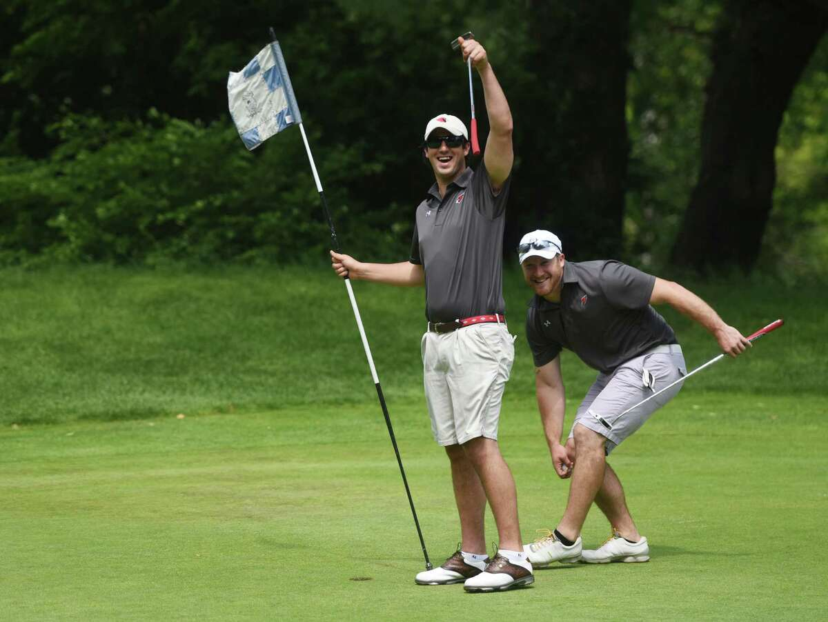 New Greenwich football head coach John Marinelli, left, and linebackers coach Jordan Capitanio celebrate after making a putt during the Greenwich High School football annual fundraiser golf tournament at E. Gaynor Brennan Golf Course in Stamford, Conn. Monday, June 8, 2015. Thirty foursomes, a total of 120 people, participated in this year's best-ball tournament to raise money for the Greenwich High School football program.