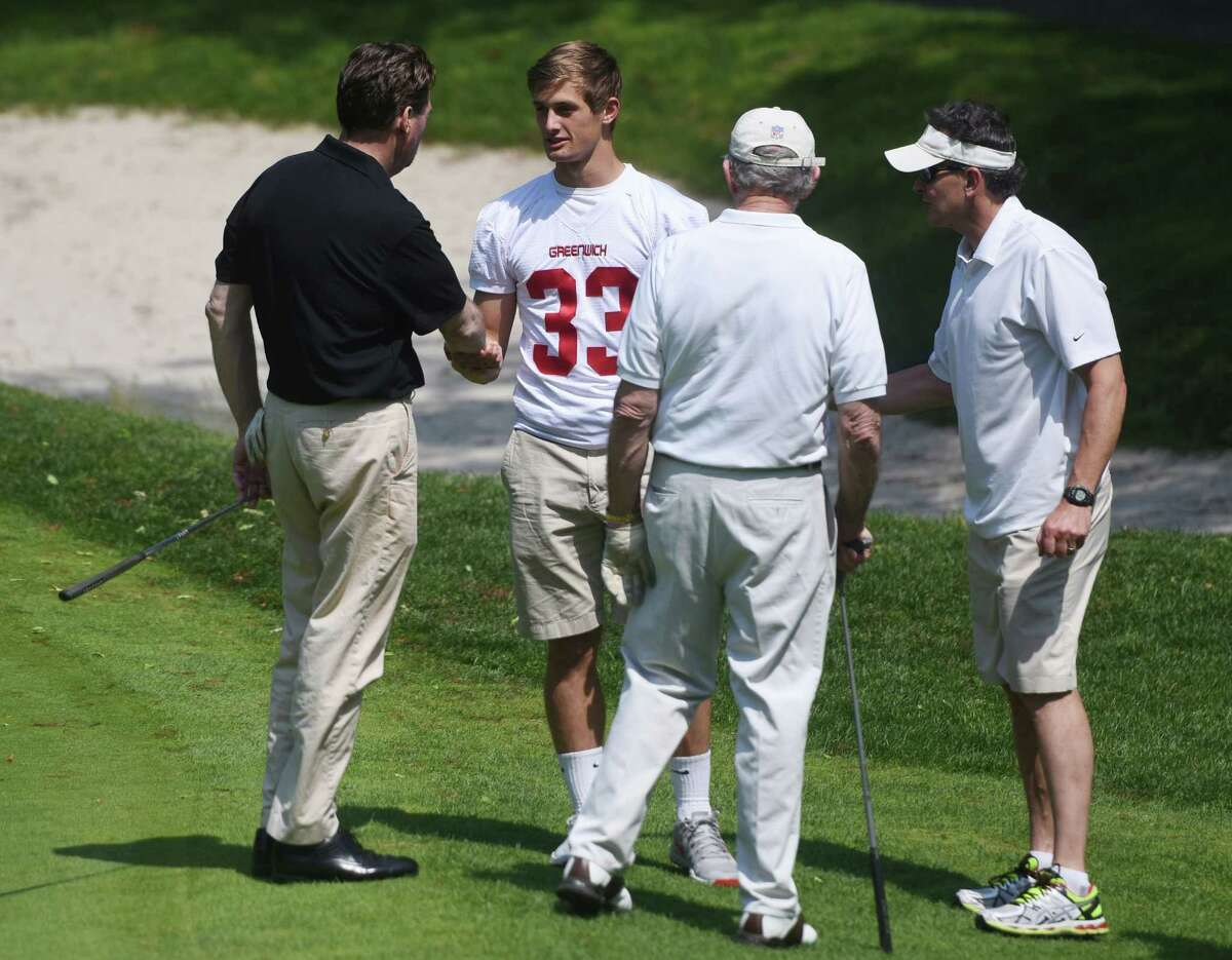 Greenwich High School rising senior running back Luke Bienstock shakes hands with Greenwich football supporters Ernie Rosato, left, Russ Warren, center, and Rusty Warren at the Greenwich High School football annual fundraiser golf tournament at E. Gaynor Brennan Golf Course in Stamford, Conn. Monday, June 8, 2015. Thirty foursomes, a total of 120 people, participated in this year's best-ball tournament to raise money for the Greenwich High School football program.