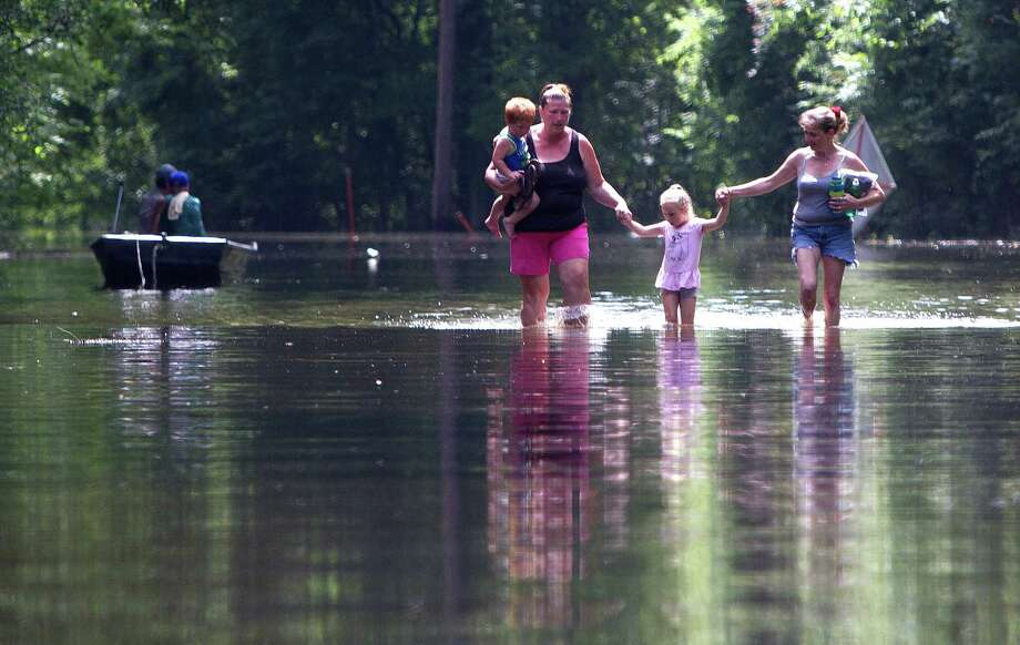 Residents of Knights Forest subdivision wade through water as they leave their homes in Hardin, Texas, on May 28. Heavy rain and increased water from the Lake Livingston Dam, has caused the Trinity River to flood. Photo: Jason Fochtman, MBR / Conroe Courier