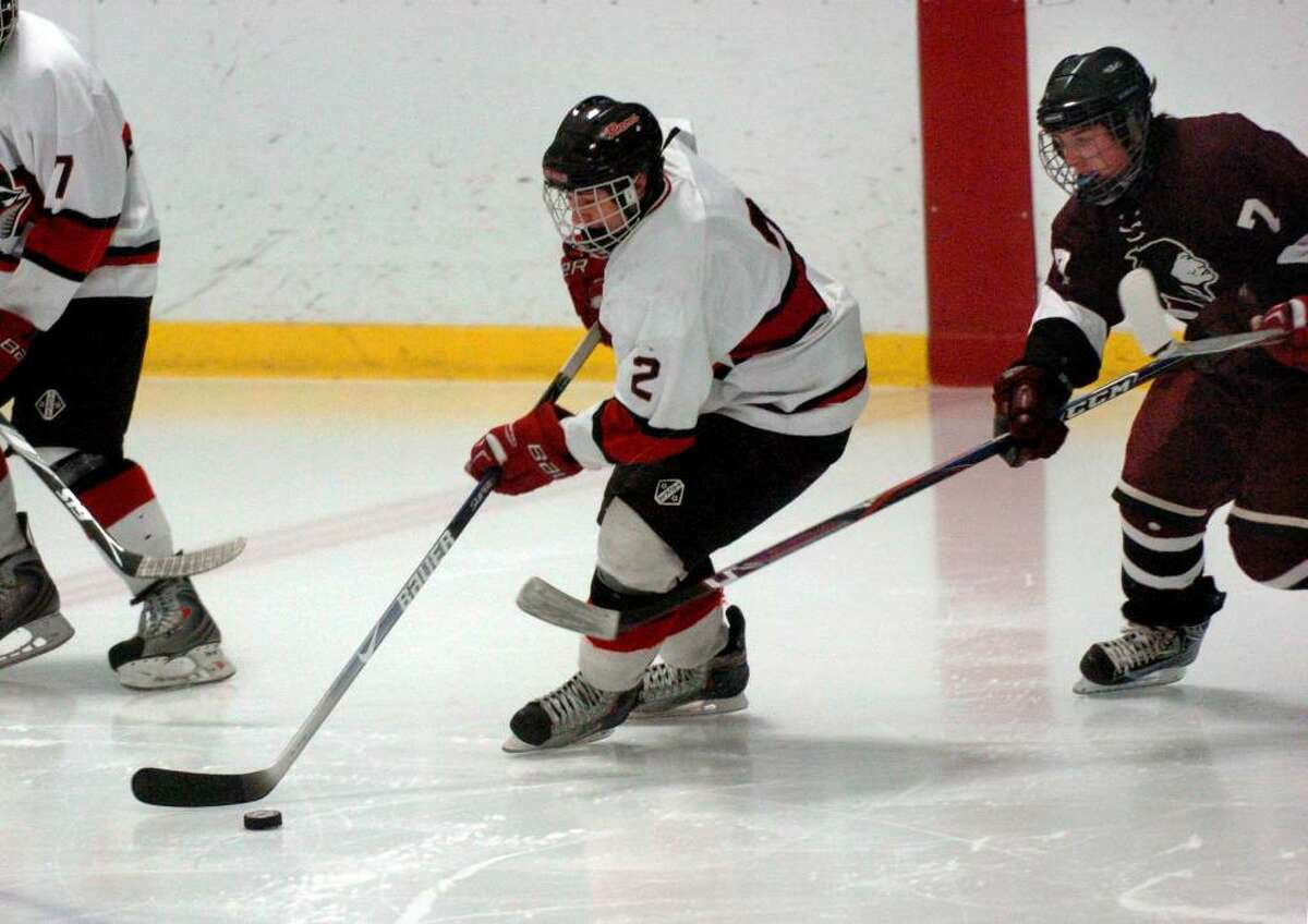 New Canaan's #2 Jimmy Joe Granito moves the puck with North Haven's #7 Tyler Benson in pursuit, during Division I Quarterfinals in Bridgeport, Conn. on Saturday Mar. 13, 2010.
