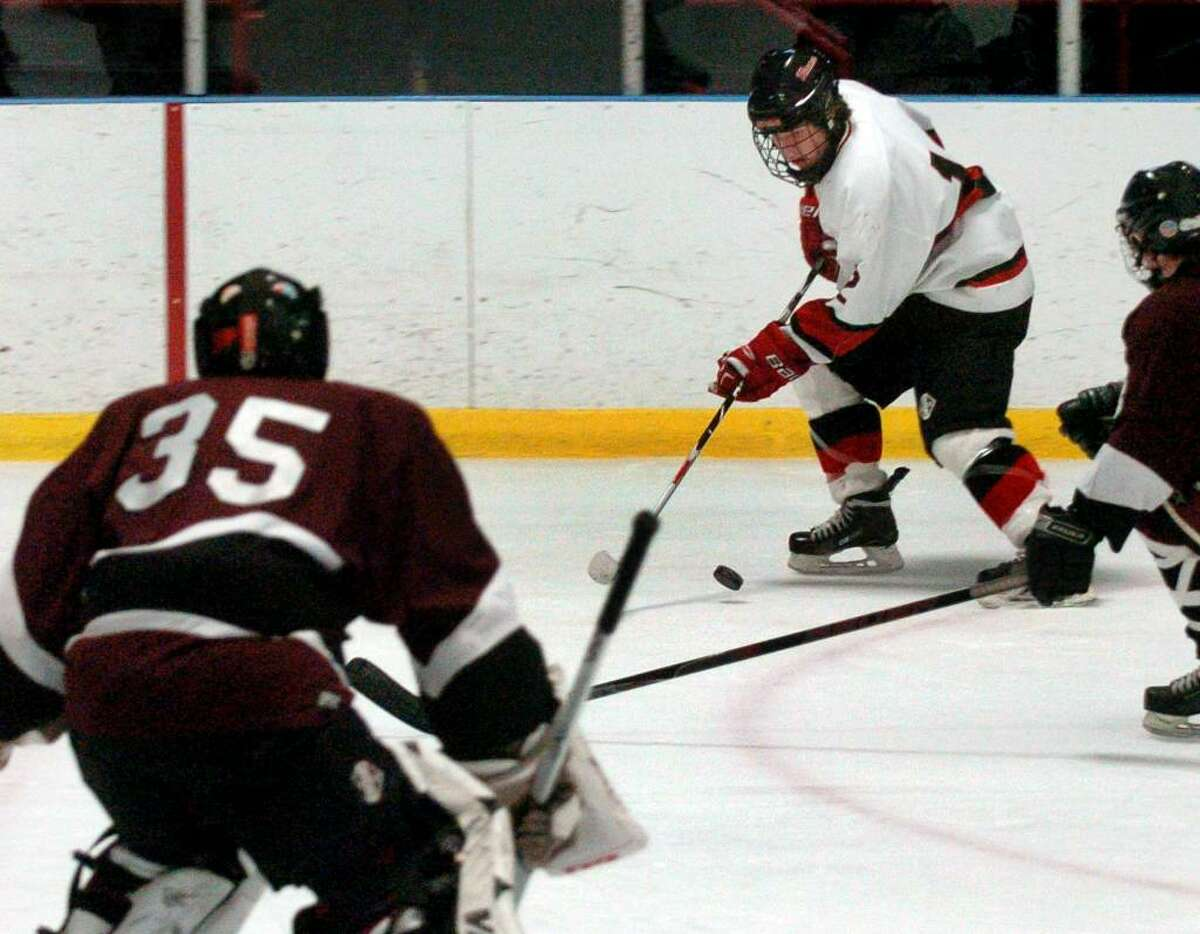 New Canaan's #12 Tim Robustelli moves the puck towards the net with North Haven goalie Mike Amarone at the ready, during Division I Quarterfinals in Bridgeport, Conn. on Saturday Mar. 13, 2010.
