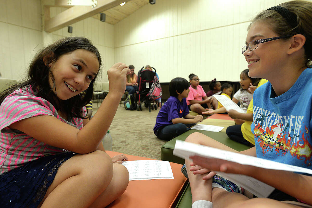 Emma Menendez (left) and Madison Stewart, both 10, joke with one another as they practice spelling out words on the first day of a summer-long sign language class for kids at Miller Library Monday. Christine Sobutka leads the course, offering two back-to-back sessions broken down by age. Photo taken Friday, June 5, 2015 Kim Brent/The Enterprise