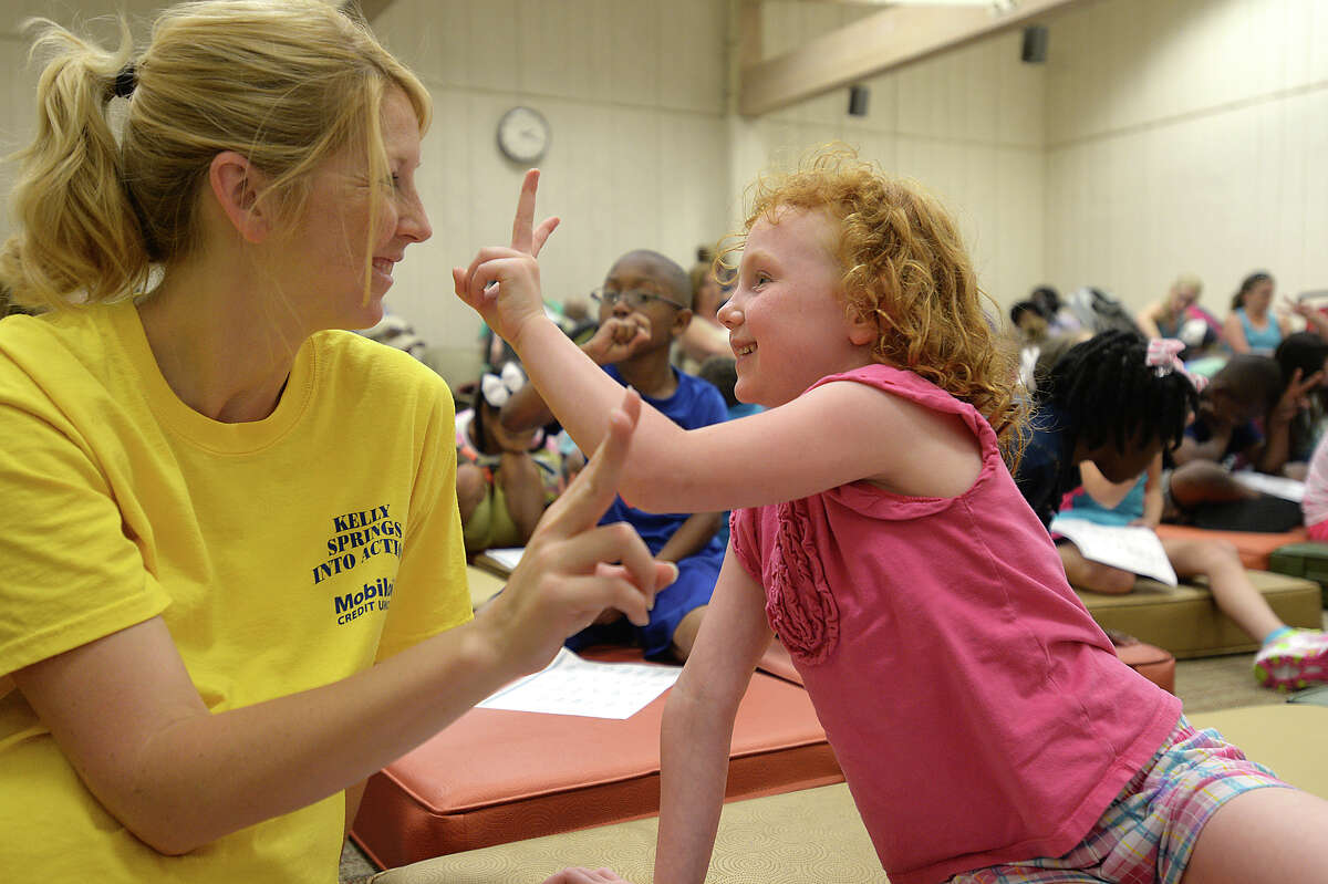 Mikki Sciba and her daughter Mary Sciba, 5, learn together how to sign letters of the alphabet on the first day of a summer-long sign language class for kids at Miller Library Monday. Christine Sobutka leads the course, offering two back-to-back sessions broken down by age. Photo taken Friday, June 5, 2015 Kim Brent/The Enterprise