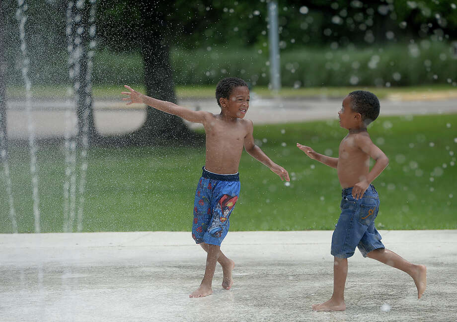 Ross Washington, 5, rushes over to join Davion Moyton, 5, amid the spouting cool waters of the splash pad in Rogers Park Monday.  Photo taken Monday, June 8, 2015 Kim Brent/The Enterprise Photo: Kim Brent / Beaumont Enterprise