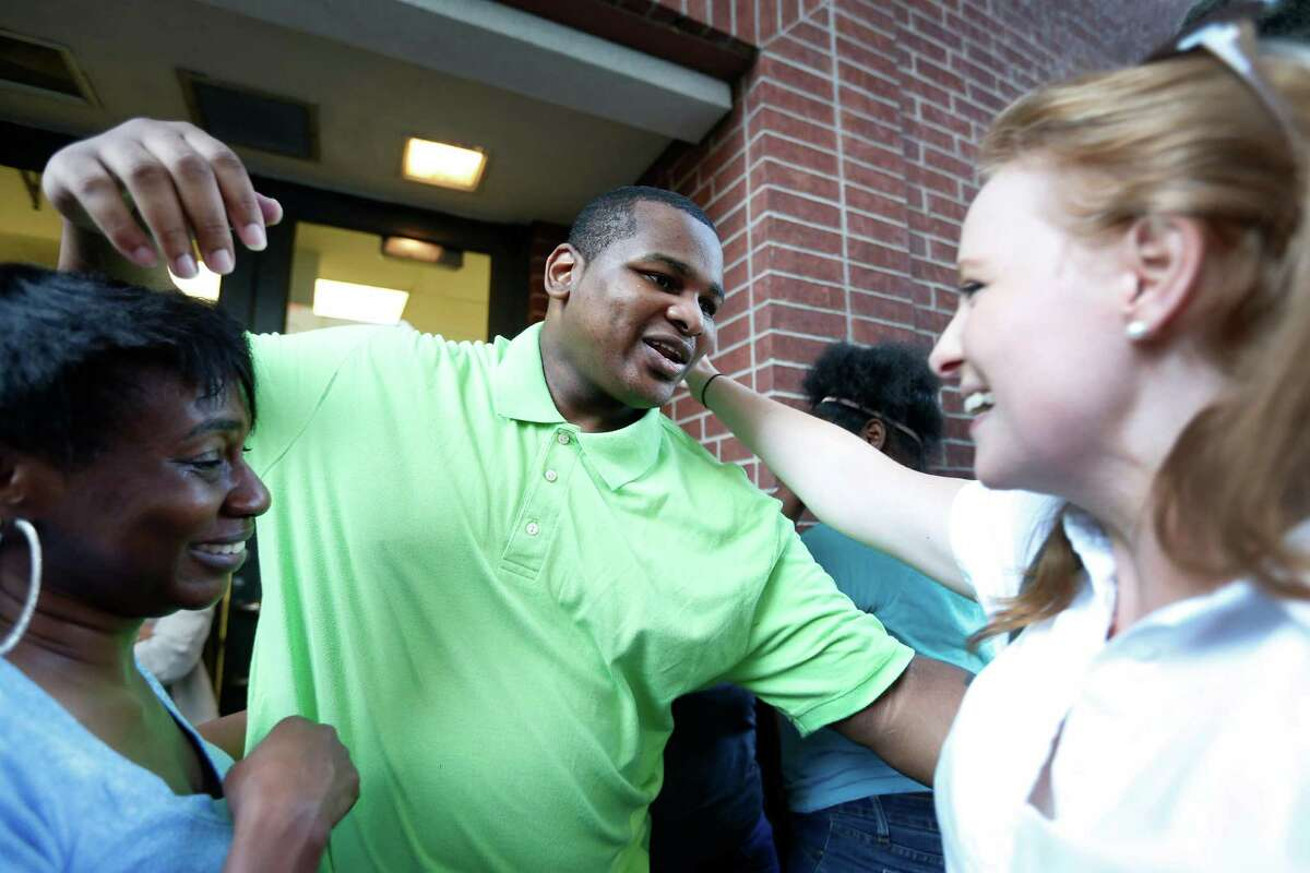 Alfred Brown reaches out to hug Houston Chronicle columnist, Lisa Falkenberg after his release from the Harris County jail on Monday, June 8, 2015, in Houston.