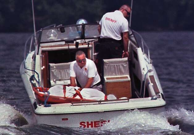 Albany County Sheriff Department First Sgt. Charles Waldo, left, sits next to the body of Gary Evans Friday, Aug. 14, 1998, in Troy N.Y., as Deputy George Travis drives the boat away from the Menands Bridge where Evans had jumped.  (Paul Buckowski/Times Union archive) Photo: PAUL BUCKOWSKI / ALBANY TIMES UNION