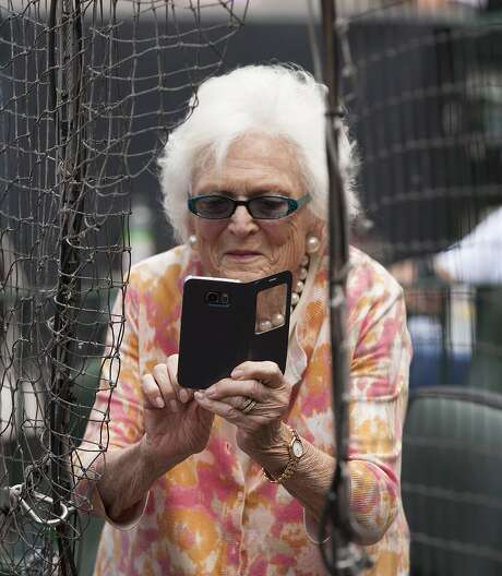 Former first lady Barbara Bush and her cell phone, before the May 3 Astros-Mariners game. Photo: George Bridges, Associated Press
