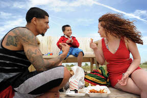 From left; Jose Torres, Jadiel Torres, 4, and Michelle Castillo, of Bridgeport, enjoy their lunch at Pleasure Beach in Bridgeport, Conn. on Sunday, May 24, 2015. The water taxi service to the beach began operation this weekend for the 2015 season.