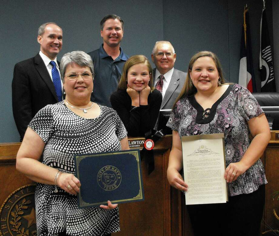 The Katy City Council and Texas Legislature presented resolutions to honor Bill Lawton, a Katy City Council member who died May 28 of cancer. From left, front row, are: Margaret Lawton, widow; Emily Adams, granddaughter; and Marisa Adams, daughter; back row: state Rep. Mike Schofield, R-Katy; Bart Adams, son-in-law; and Fabol Hughes, Katy mayor. Photo: Trish Johnson