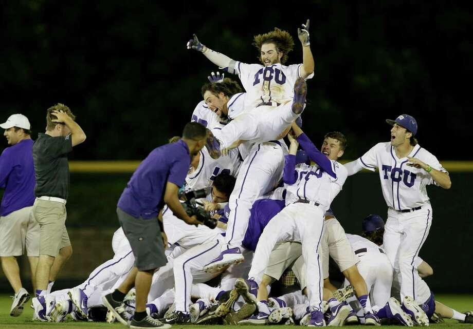 TCU 's Garrett Crain, center, celebrates with teammates following the 16th inning of a super regional of the NCAA college baseball tournament against Texas A&M in Fort Worth, Texas, Monday, June 8, 2015. TCU won 5-4. Photo: Tim Sharp /Associated Press / FR62992 AP