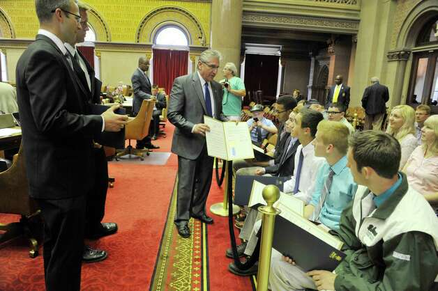Assemblyman Jim Tedisco, center, hands out copies of an Assembly resolution recognizing members of the Shenendehowa High School boys track and field team at the Assembly chambers at the Capitol on Monday, June 8, 2015, in Albany, N.Y. Track team members are, from top to bottom on right, Shawn Bleichert, Collin Rowe, Mitchell Halpern, Tyler Schmidt and Connor Buhrmeister. On the left are Jason Burlingame, left, head coach and sprint coach and Lance Jordan, distance coach. Bleichert won the 55 meter hurdles and the other members of the team won the 4 x 800 relay.    (Paul Buckowski / Times Union) Photo: PAUL BUCKOWSKI / 00032200A