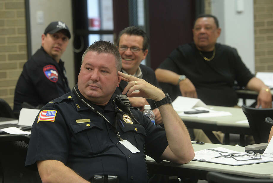 Law enforcement, including Beaumont Police officer John Cross, and community members listen as they review scenarios during a sensitivity training session led by U.S. Department of Justice Regional Director Synthia Taylor at the Beaumont Police station Tuesday. Chief James Singletary said the course had a dual purpose, as it also addressed the department's partnering with the local NAACP and 100 Black Men groups to  tackle the issue of minority recruitment. Photo taken Tuesday, June 9, 2015 Kim Brent/The Enterprise Photo: Kim Brent / Beaumont Enterprise