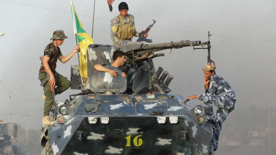 Iraqi Federal police and Shiite Hezbollah Brigade militiamen patrol on the front line in eastern Husaybah, 8 kilometers (5 miles) east of Ramadi, Iraq. Photo: Uncredited, Associated Press